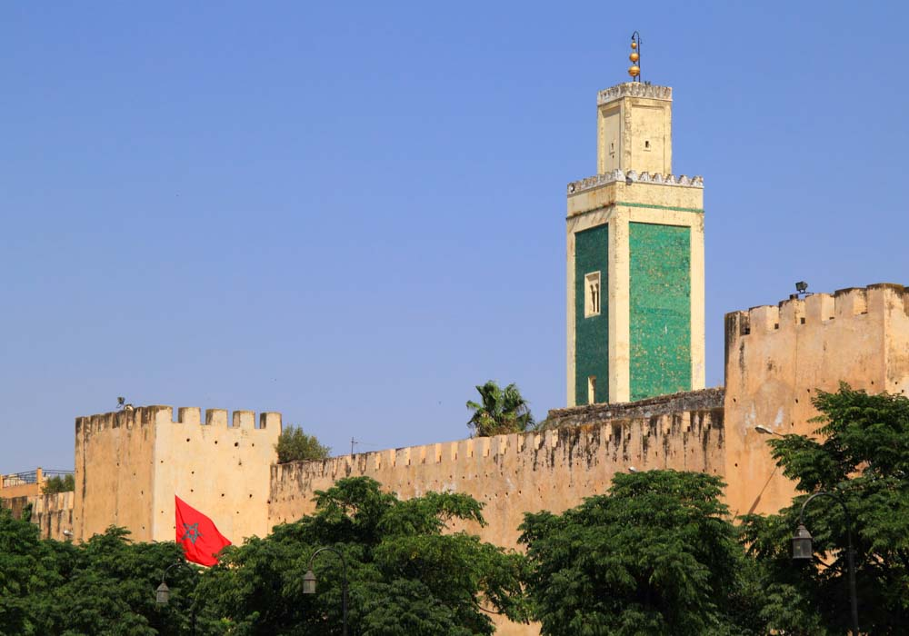Morocco, Meknes, Historical city wall and mosque minaret in Arabesque design
