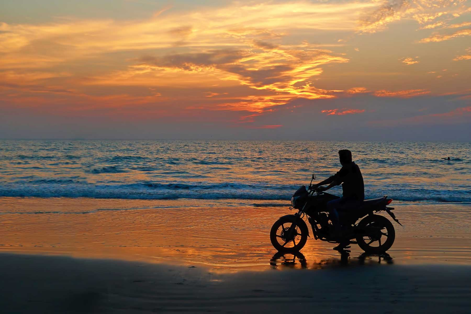 Motorcyclist at sunset on the beach.