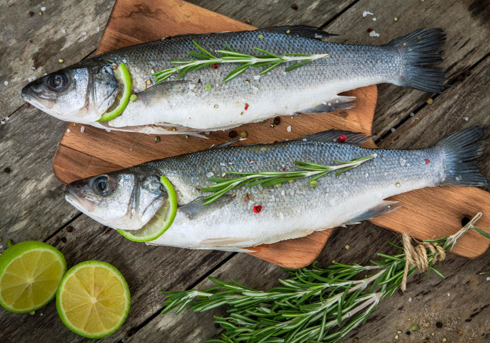 Two raw seabass with lime and rosemary on the wooden background