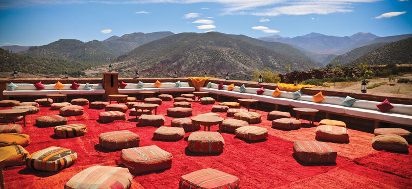 relax on cushions under blue skies with a view of atlas mountains