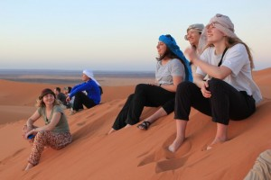 People sitting on a dune in the Sahara
